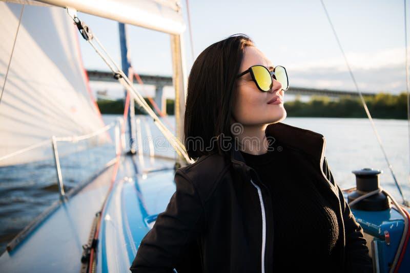 A jovem mulher bonita senta-se na bacia e nas poses do iate Veste sunglusses com mão e sorriso O modelo está navegando a bordo fotos de stock royalty free