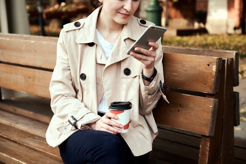 A jovem mulher bonita senta-se no banco de madeira, guarda a xícara de café afastada, usando o smartphone imagens de stock
