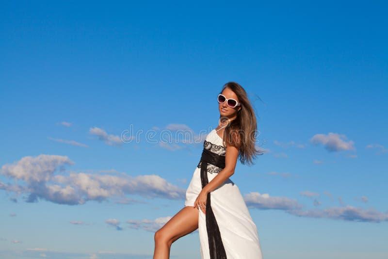 Jovem mulher bonita sobre o céu azul fotografia de stock royalty free
