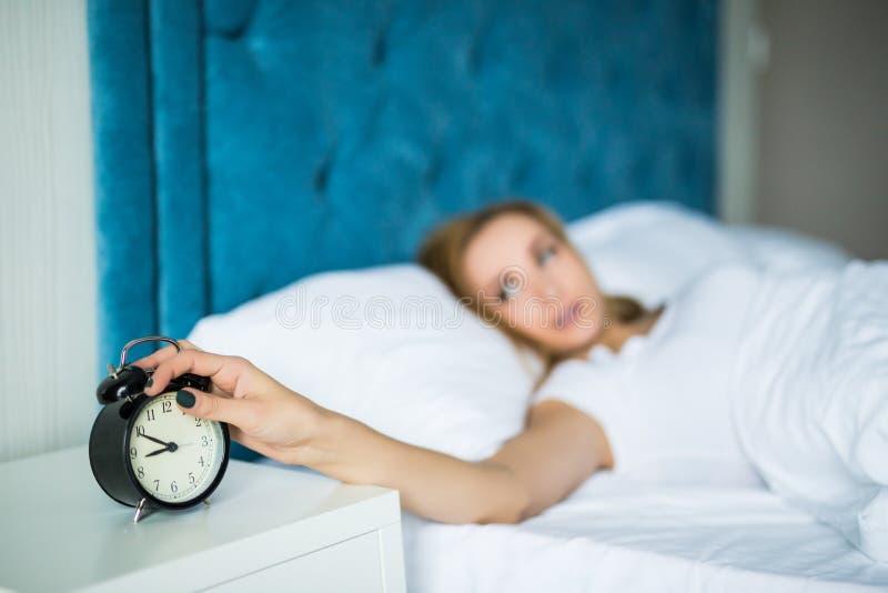 Jovem mulher bonita sonolento na cama com mão de alargamento fechado dos olhos ao despertador em casa imagem de stock royalty free