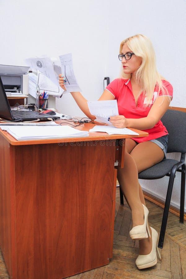 A jovem mulher bonita trabalha no escritório fotos de stock