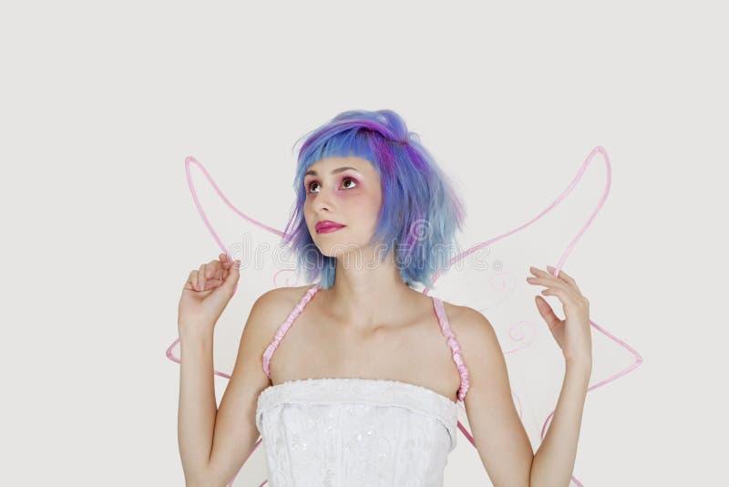 Jovem mulher bonita vestida como o anjo com o cabelo tingido que olha acima contra o fundo cinzento fotografia de stock