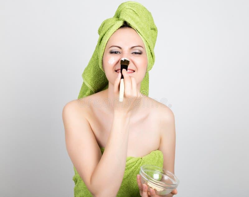 A jovem mulher bonita vestida em uma toalha de banho faz uma máscara cosmética na cara indústria da beleza e cuidados com a pele  imagens de stock royalty free