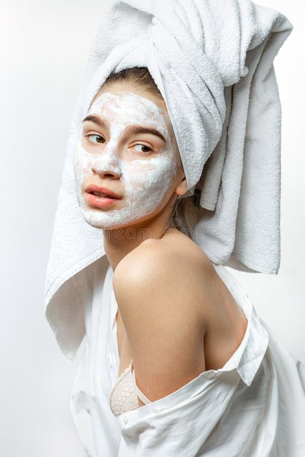 A jovem mulher bonita vestida na roupa branca com uma toalha branca em seu cabelo e m?scara cosm?tica em sua cara guarda-a fotografia de stock royalty free