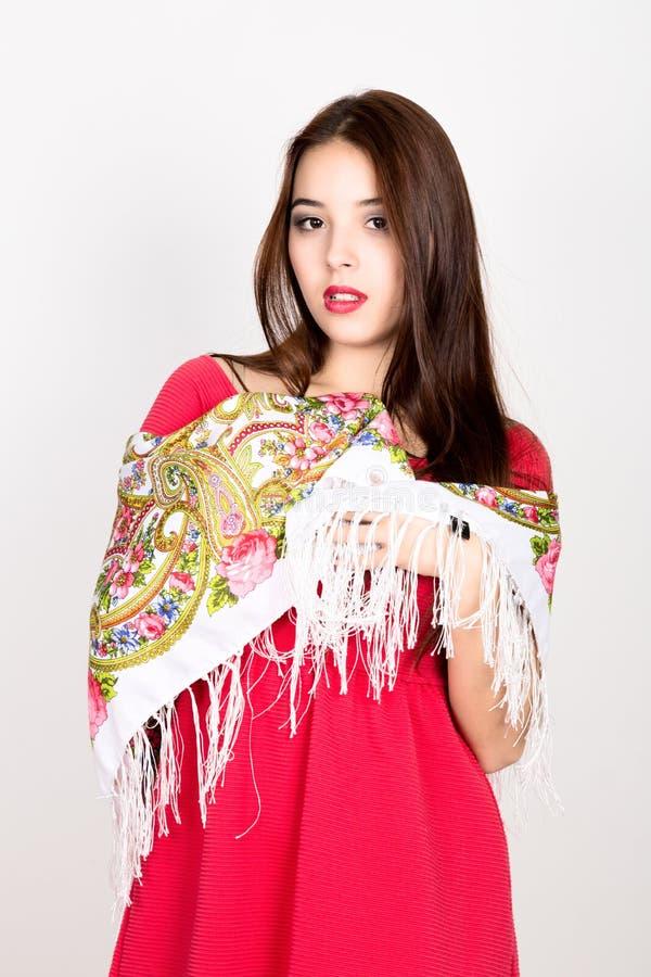 A jovem mulher bonita vestiu-se em um vestido vermelho e coloriu-se o lenço que levanta no estúdio imagens de stock royalty free