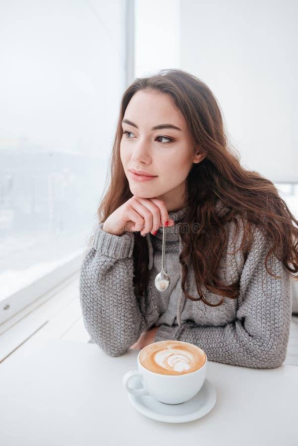 A jovem mulher bonita vestiu-se na camiseta que senta-se no café fotografia de stock
