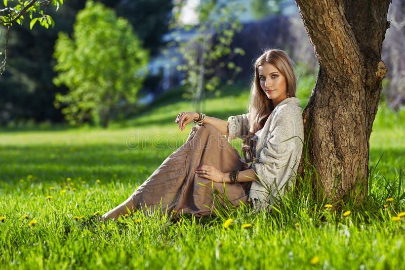 A jovem mulher bonita vestiu-se no estilo do boho que senta-se no gra verde foto de stock