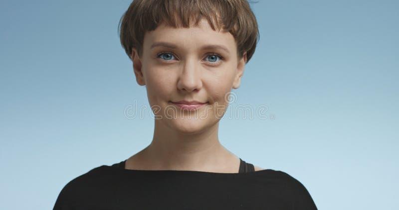Jovem mulher bonito com cabelo curto em fundos coloridos imagem de stock