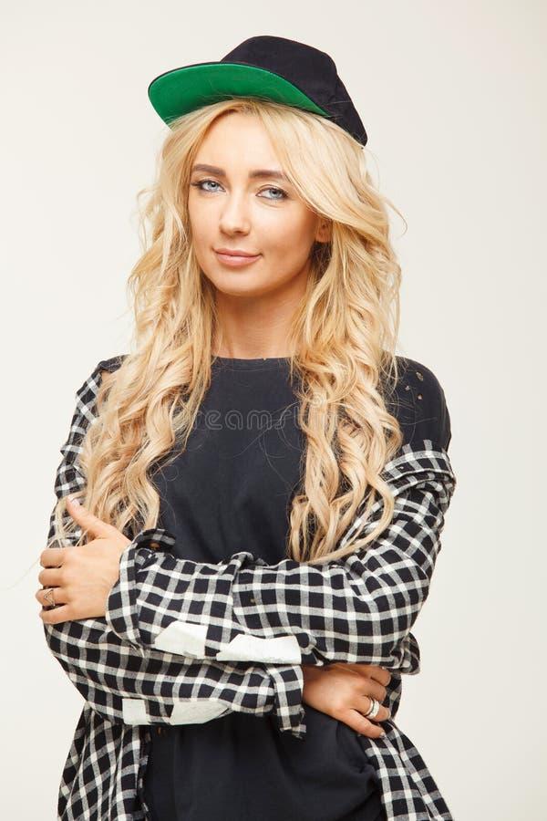 Jovem mulher bonito com cabelo louro volumoso no boné de beisebol e na camisa retrato bonito de uma menina à moda imagens de stock