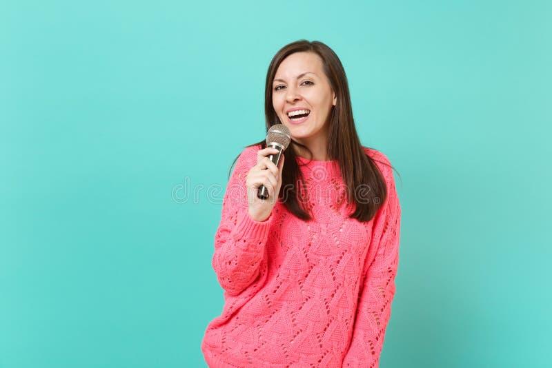 A jovem mulher bonito de sorriso na camiseta cor-de-rosa feita malha que guarda à disposição e canta a música no microfone isolad imagem de stock