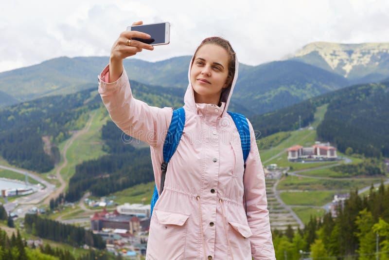 Jovem mulher bonito deleitada com sorriso agradável em sua posição da cara na parte superior do monte, guardando seu smartphone,  foto de stock