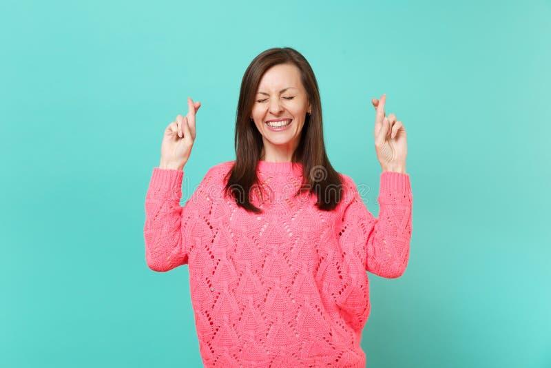 A jovem mulher bonito na camiseta cor-de-rosa feita malha que mantém os dedos cruzou os olhos fechados para fazer o desejo isolad imagens de stock