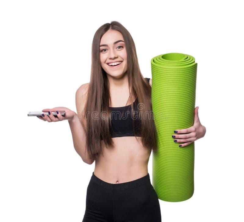 Jovem mulher bonito no sportswear com a esteira verde pronta para o exercício Sorriso e fala no telefone Isolado no fundo branco foto de stock royalty free