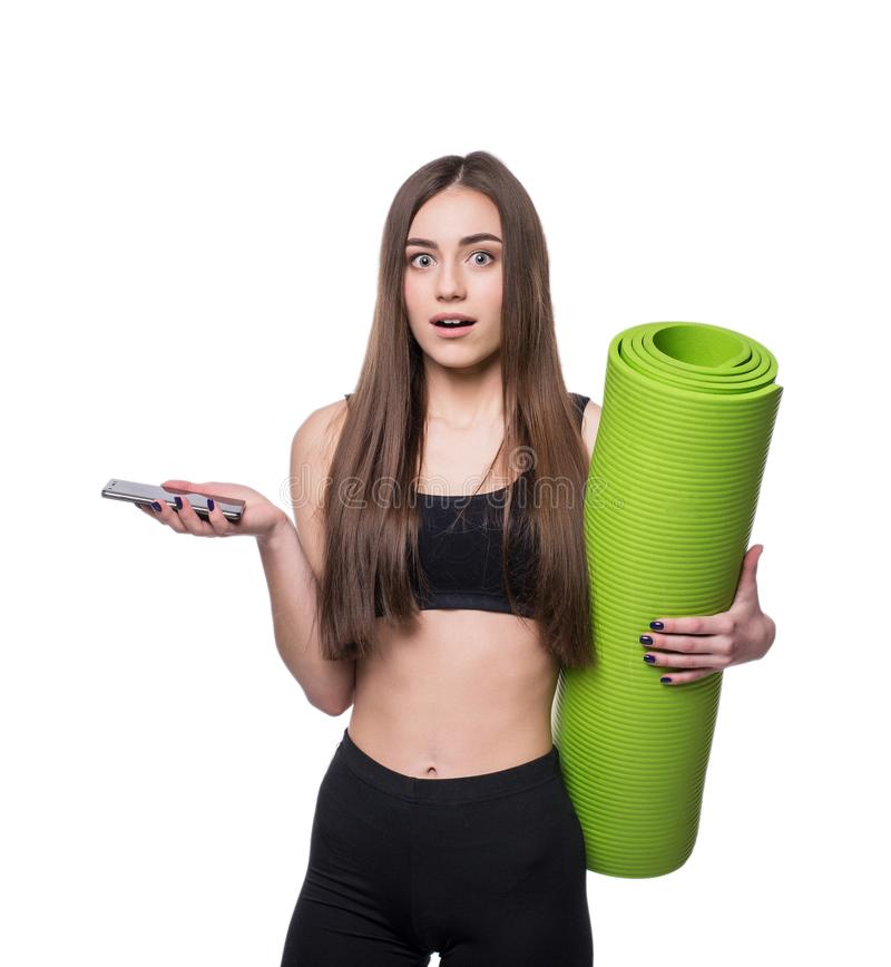 Jovem mulher bonito no sportswear com a esteira verde pronta para o exercício Sorriso e fala no telefone Isolado no fundo branco imagens de stock royalty free