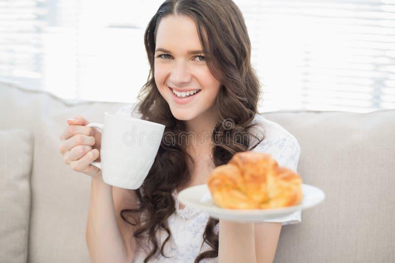 Jovem mulher bonito nos pyjamas que comem o café da manhã imagem de stock royalty free