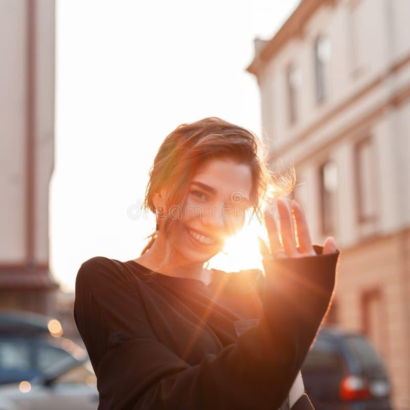 A jovem mulher bonito positiva engraçada no t-shirt preto do vintage é de levantamento e de sorriso perto das construções do vint imagens de stock