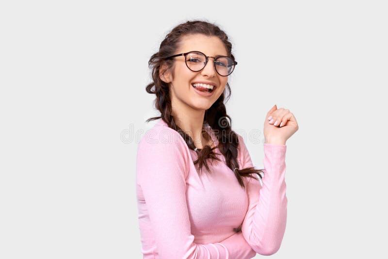 A jovem mulher bonito positiva que sorri amplamente, veste a blusa ocasional cor-de-rosa e espetáculos transparentes redondos, so foto de stock