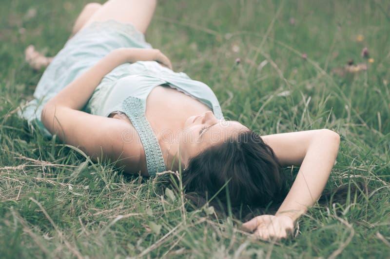 Jovem mulher bonito que encontra-se na grama no dia de verão foto de stock royalty free