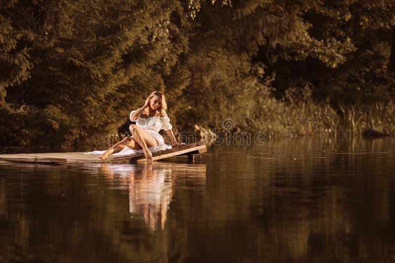 Jovem mulher bonito que senta-se pelo lago que toca na água por seu pé imagem de stock
