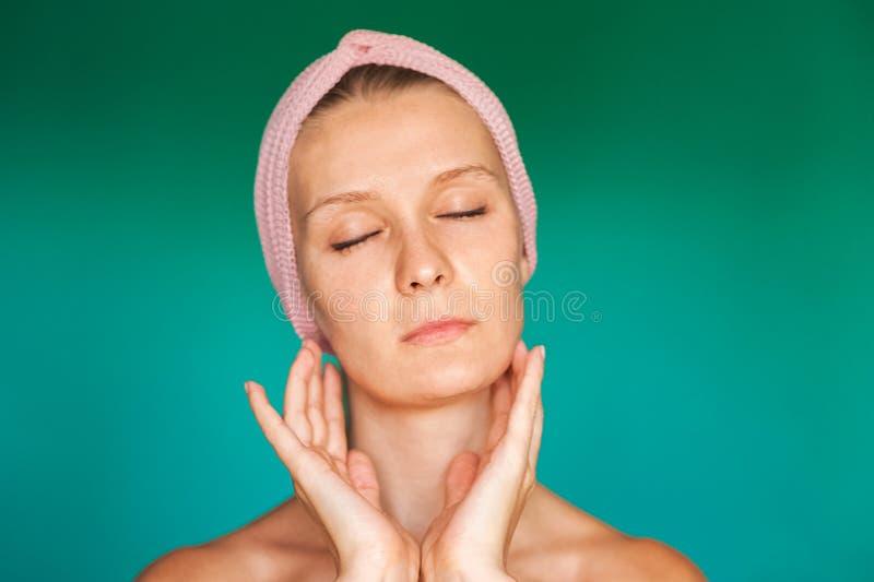 A jovem mulher branca põe sobre uma máscara protetora em casa sobre um fundo de turquesa Mulher europeia que lava sua cara com fi foto de stock