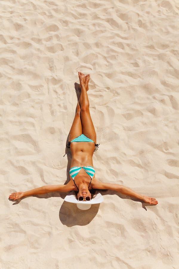 Jovem mulher bronzeada no biquini na areia da praia fotografia de stock royalty free
