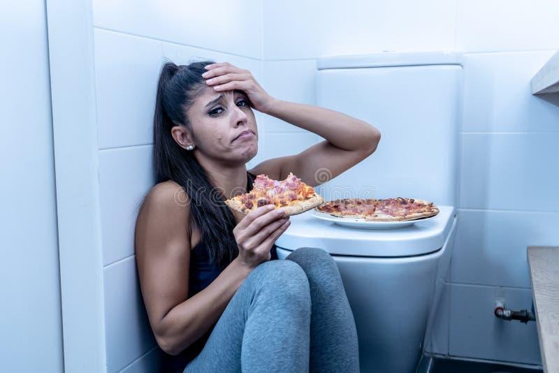 Jovem mulher bulímica nova e triste atrativa que sente comer culpado e doente ao sentar-se no assoalho ao lado do toalete dentro foto de stock royalty free