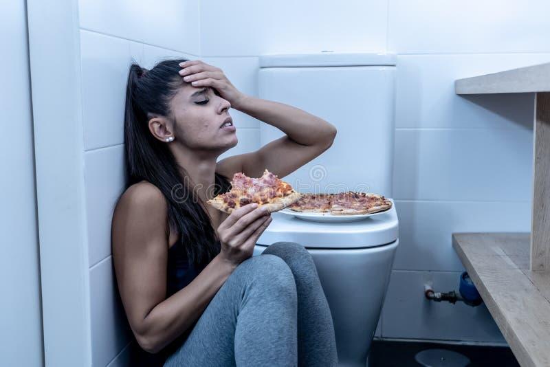 Jovem mulher bulímica nova e triste atrativa que sente comer culpado e doente ao sentar-se no assoalho ao lado do toalete dentro fotos de stock