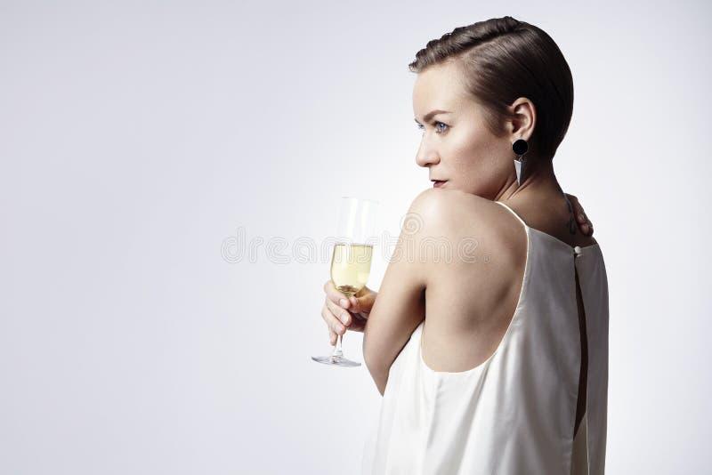 Jovem mulher, cabelo curto, comemorando com champanhe Ano novo, conceito do Natal imagem de stock royalty free
