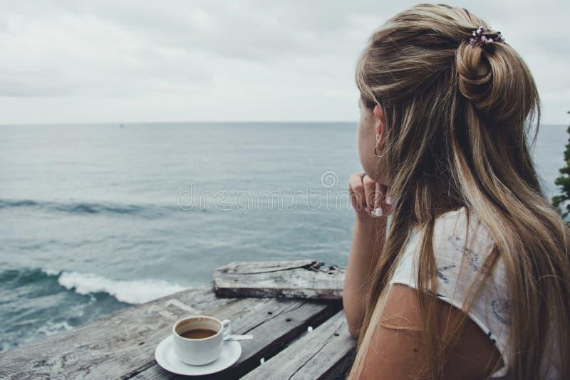 Jovem mulher café que relaxa, beber e apreciando a vista do oceano, Bali indonésia foto de stock