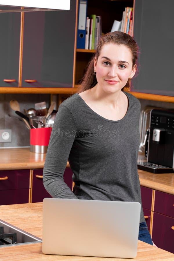 Jovem mulher calma na cozinha que trabalha no computador para o comércio eletrónico foto de stock royalty free