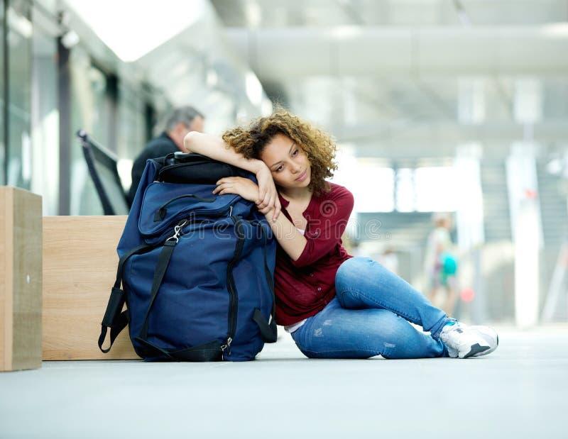 Jovem mulher cansado que descansa no saco foto de stock royalty free