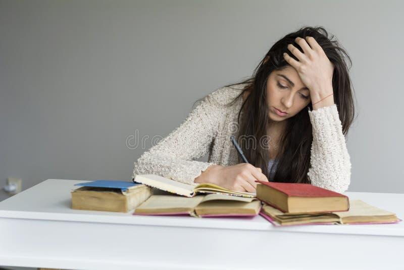 jovem mulher cansado que senta-se em sua mesa com os livros na parte dianteira foto de stock