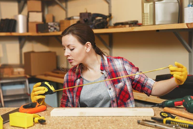 Jovem mulher caucasiano bonita que trabalha na oficina da carpintaria no lugar da tabela imagens de stock royalty free