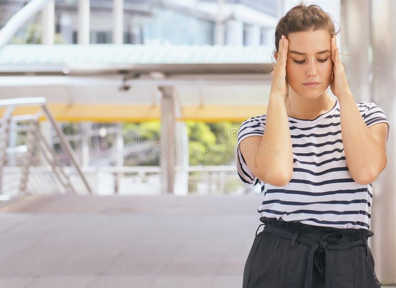 A jovem mulher caucasiano bonita tem uma dor de cabeça e comprime-a em exterior fotos de stock