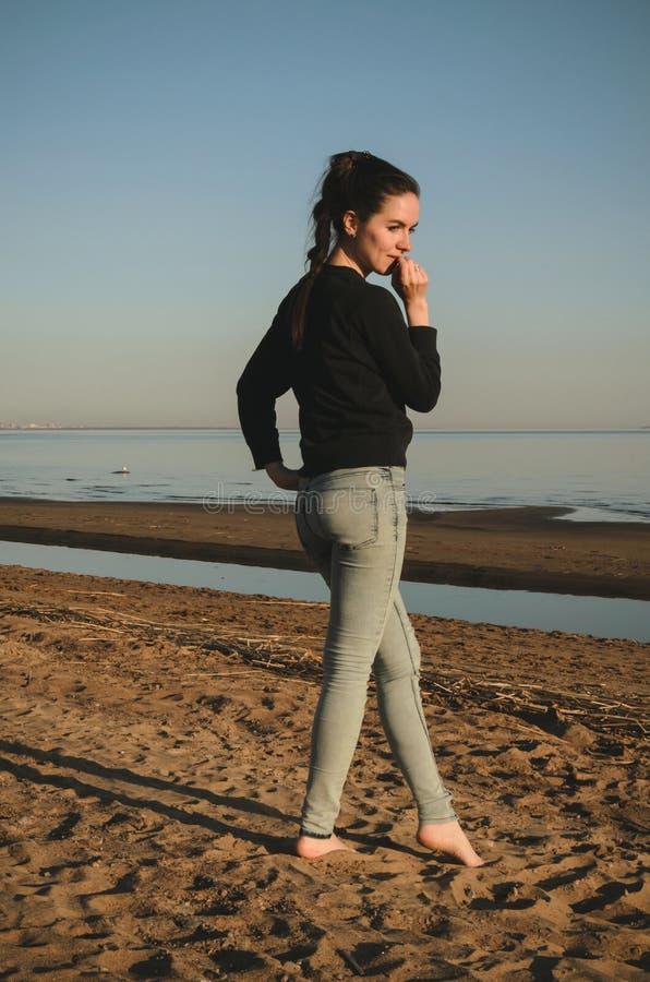 Jovem mulher caucasiano na camisa de suor preta, calças de ganga andando apenas na praia no por do sol Retrato exterior pensativo fotografia de stock