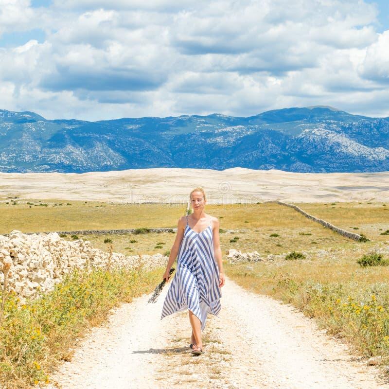 Jovem mulher caucasiano no ramalhete da terra arrendada do vestido do verão de flores da alfazema ao andar exterior com rochoso s foto de stock royalty free