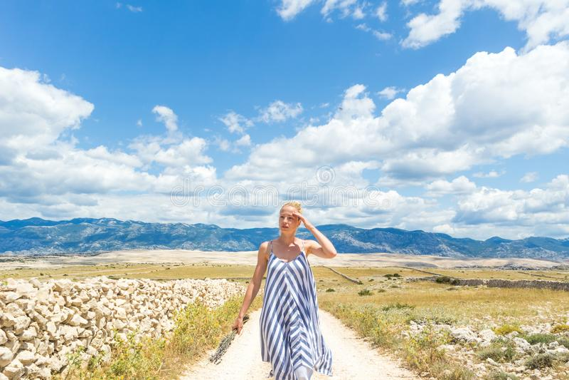 Jovem mulher caucasiano no ramalhete da terra arrendada do vestido do verão de flores da alfazema ao andar exterior com rochoso s fotografia de stock royalty free
