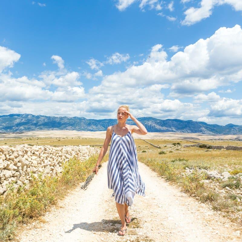 Jovem mulher caucasiano no ramalhete da terra arrendada do vestido do verão de flores da alfazema ao andar exterior com rochoso s imagem de stock royalty free