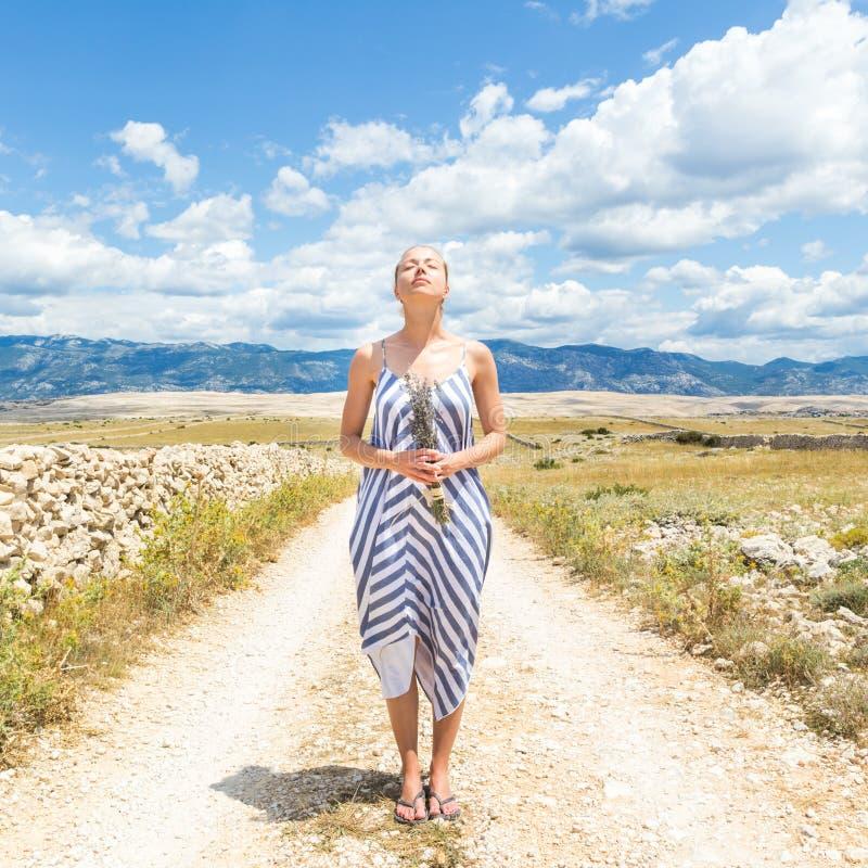 Jovem mulher caucasiano no ramalhete da terra arrendada do vestido do verão de flores da alfazema que aprecia a natureza mediterr fotografia de stock royalty free