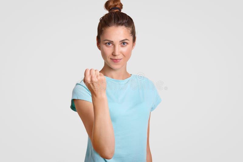 A jovem mulher caucasiano restrita séria mostra o punho na câmera, adverte-o sobre a punição, mostra-lhe o poder, vestido na roup imagens de stock royalty free