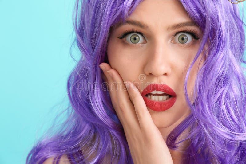 Jovem mulher chocada com cabelo incomum no fundo da cor foto de stock