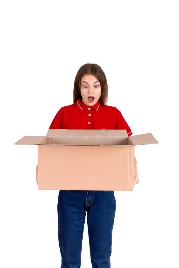 A jovem mulher chocada está olhando o pacote faltado da caixa isolada no fundo branco fotos de stock