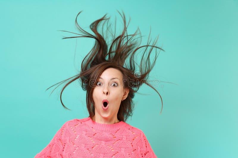 Jovem mulher chocada na camiseta cor-de-rosa feita malha com o cabelo de vibração que mantém a boca largamente aberta, olhando su foto de stock