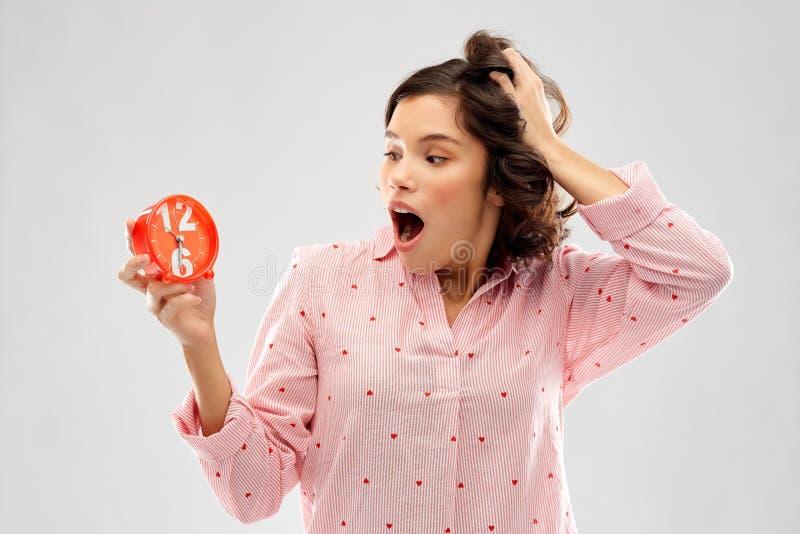 Jovem mulher chocada no pijama com despertador imagem de stock royalty free