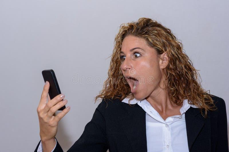 Jovem mulher chocada que olha fixamente em seu móbil foto de stock royalty free