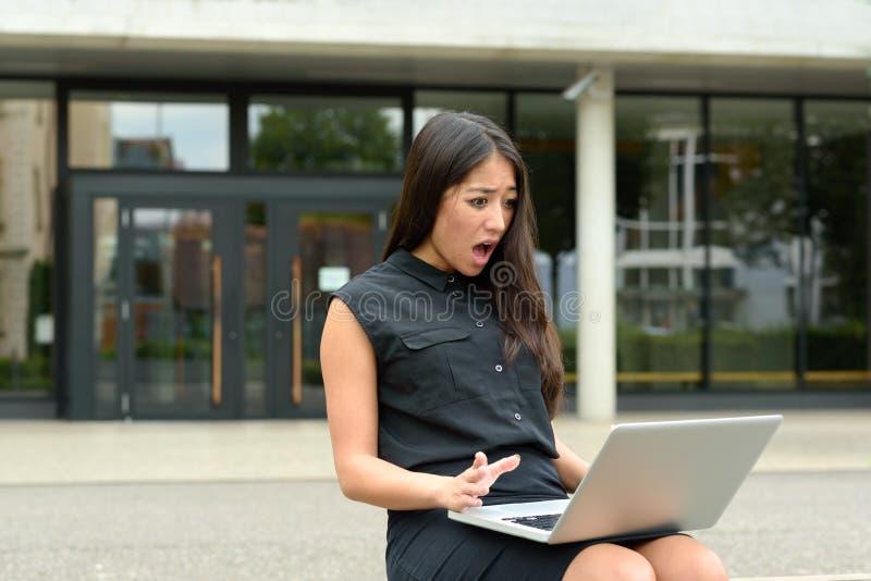 Jovem mulher chocada que olha fixamente em seu portátil foto de stock