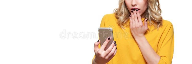 Jovem mulher chocada que sustenta seu telefone celular, lendo notícia chocante Mulher na incredulidade, isolado sobre o branco foto de stock