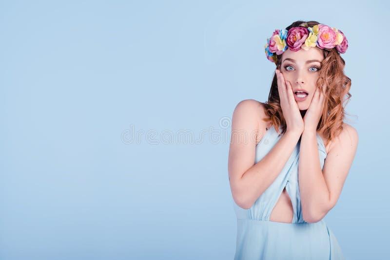 Jovem mulher chocado que veste claro isolado da tiara da faixa coroa floral - grinalda azul da flor do fundo das flores na cabeça foto de stock royalty free