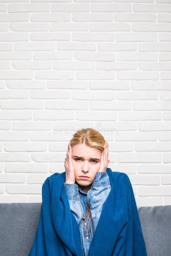 Jovem mulher coberta com a cobertura que sofre do frio em casa fotos de stock