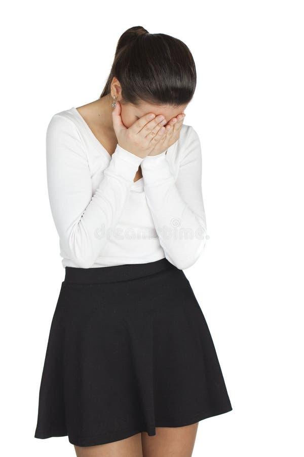 A jovem mulher cobre sua cara com suas mãos no sofrimento foto de stock